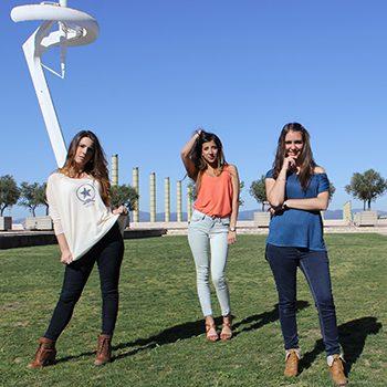 Tres chicas con la torre de comunicaciones al fondo